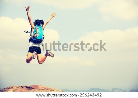 young asian woman jumping on mountain peak cliff - stock photo