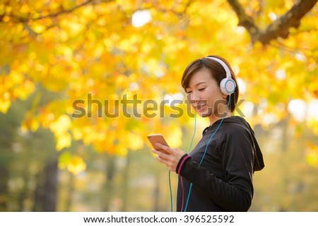 Young Asian woman listen to music with a smart phone. - stock photo