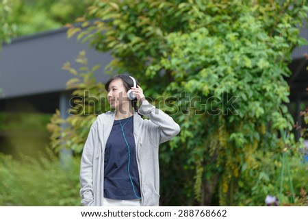 Young Asian woman listening to music. - stock photo
