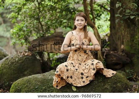 young asian woman meditating in tropical nature, thailand - stock photo