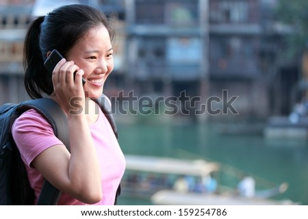 young asian woman on the phone at fenghuang ancient town,china  - stock photo