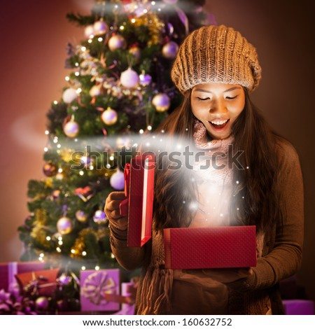 Young Asian woman opening a present full of Christmas magic. - stock photo