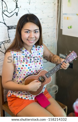 Young Asian woman playing ukulele - stock photo