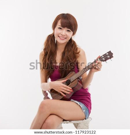 Young Asian woman playing ukulele isolated on white background. - stock photo