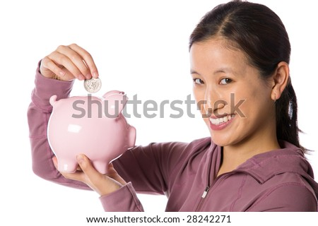 Young asian woman putting money into a piggy bank