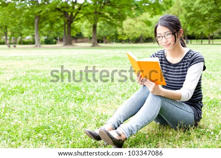 young asian woman reading a book in the park