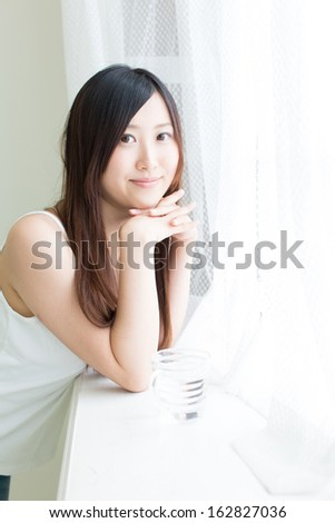 young asian woman relaxing in sunny room