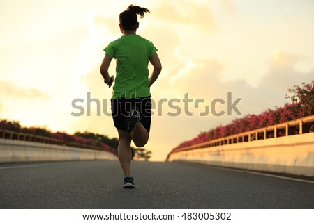 young asian woman runner running on road