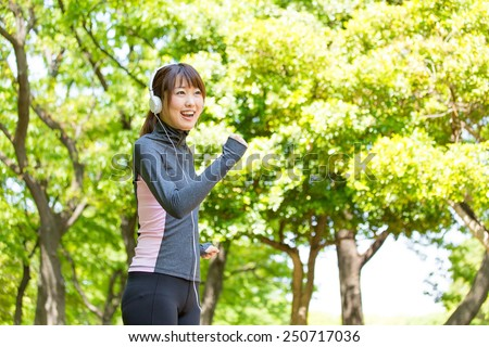 young asian woman running in the park - stock photo