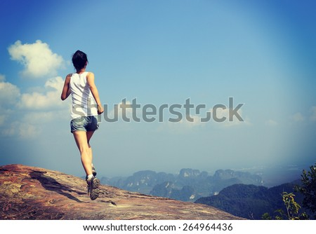young asian woman running on mountain peak cliff - stock photo