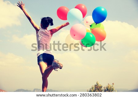 young asian woman running on mountain peak rock with colored balloons  - stock photo