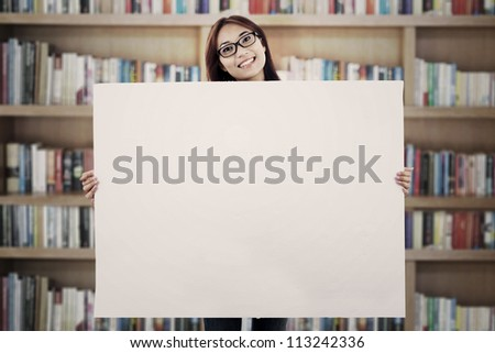 Young asian woman showing blank white board that can be used as copy space - stock photo