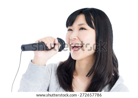 young Asian woman singing with microphone, isolated on white background
