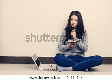 Young Asian woman sitting by the wall with hand holding notebook and pen, working with laptop, doubtful emotion. - stock photo