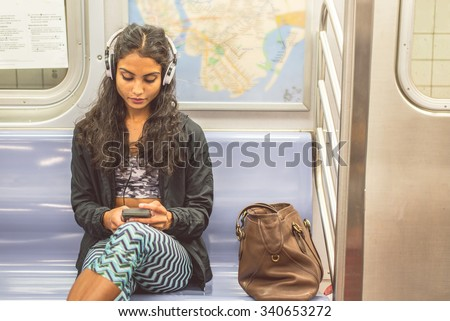 Young asian woman sitting in a subway car and listening music with her smartphone - Pretty girl riding on a train and going to work - stock photo
