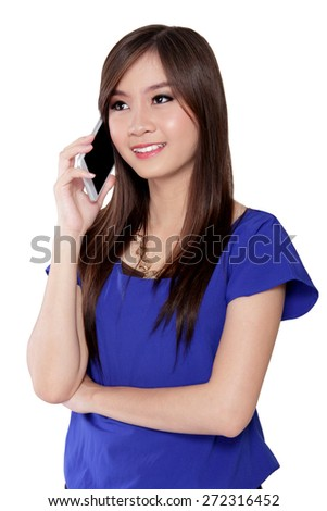 Young Asian woman smiling while talking on her mobile phone, isolated on white background - stock photo