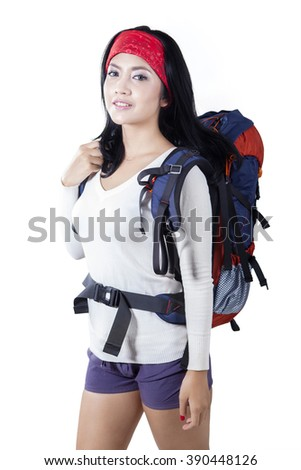 Young Asian woman standing in the studio while carrying a hiking bag and smiling at the camera, isolated on white background - stock photo