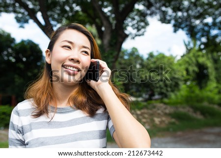 Young asian woman talking on phone at outdoor - stock photo