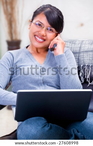 Young Asian woman talking on the phone facing the camera while using her laptop - stock photo