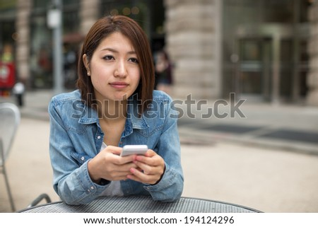 Young Asian woman texting on cellphone in a city