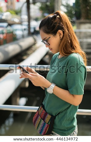 Young Asian woman texting on the smart phone.