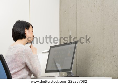Young Asian woman thinking to watch a desktop computer.