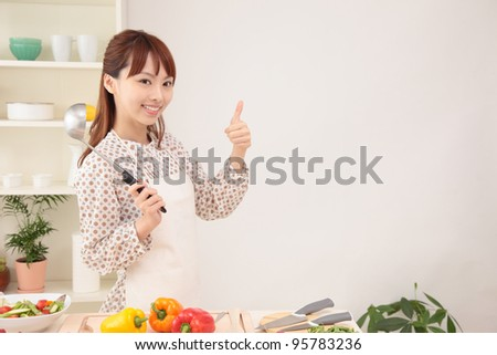 Young Asian woman to make a finger in the kitchen - stock photo