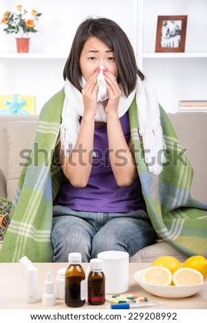 Young asian woman treats colds. Medicines and lemons on the table. - stock photo
