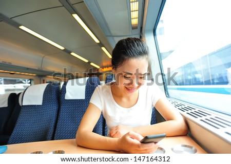 young asian woman use smartphone interior of train/subway
