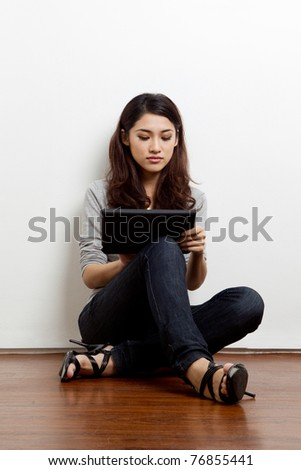 young asian woman using a tablet - stock photo