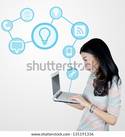 Young Asian woman using laptop computer with technology icons and symbols - stock photo