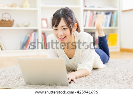 young asian woman using laptop in the room - stock photo