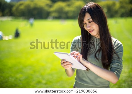 Young Asian Woman using tablet pc computer outdoor in a park