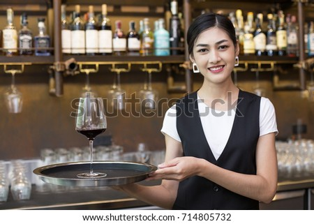 Young Asian Woman Waiter Restaurant Catering Service Happy Emotion. Woman Waiter Present Red-Wine for Customer at Bar. Woman with Wine in Bar Concept.