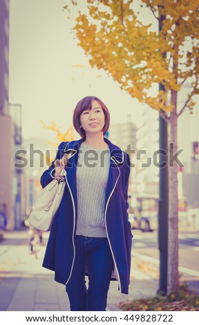 Young Asian woman waking on a city corner. - stock photo