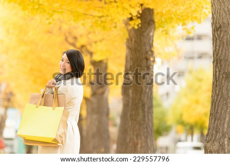 Young Asian woman walking along an avenue lined with ginkgo trees. - stock photo
