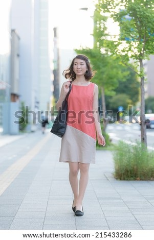 Young Asian woman walking on sidewalk
