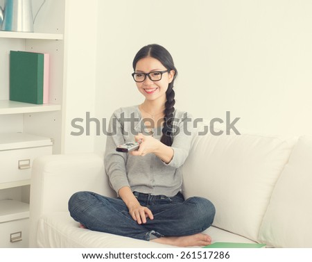 young asian woman watching horror movie with suspense look tv in the room