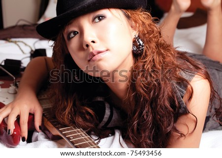 Young asian woman with a red guitar. - stock photo