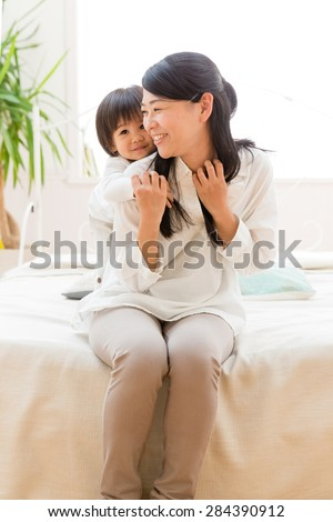 young asian woman with baby on the bed room - stock photo