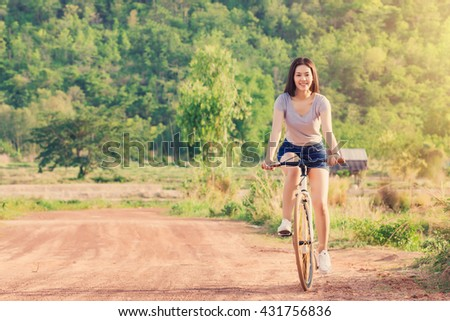 Young Asian woman with vintage bicycle in countryside nature landscape. - stock photo