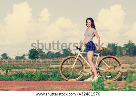 Young Asian woman with vintage bicycle in countryside nature landscape.