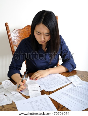 Young Asian woman working on her US Income Tax return for the IRS - seated at a table with papers spread out in front of her - appears confused about receipt
