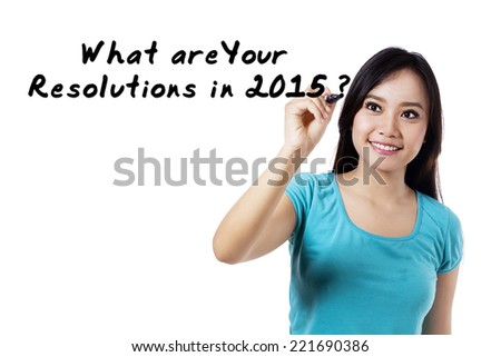 Young asian woman writes a question of resolutions in 2015 - stock photo