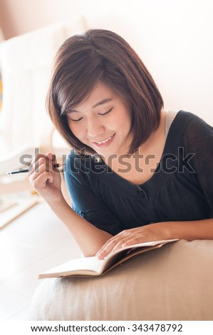Young asian woman writing memo diary note in casual dress. - stock photo