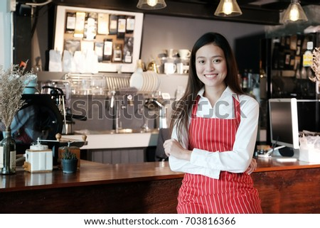 Young asian women Barista standing with smiling face in font of cafe counter background, small business owner, food and drink industry concept