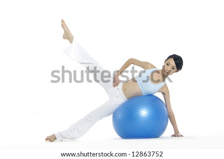 young Asian women working out with gym ball - stock photo