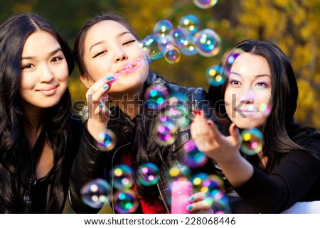 Young Asian Womens Blowing Bubbles in the park. - stock photo
