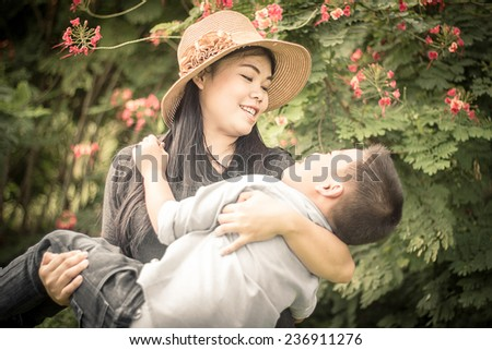 Young Asians woman Carrying Her son. - stock photo