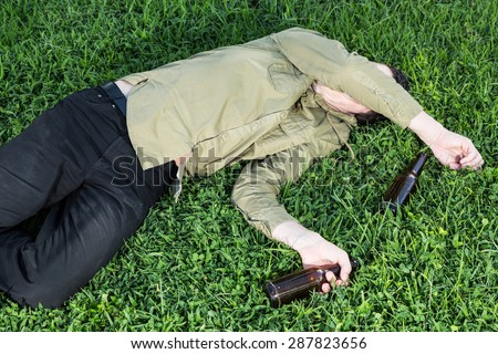 Young asleep or drunk, outdoors on the grass in the park - stock photo